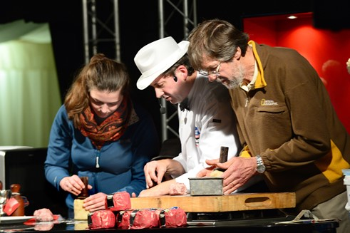 Melton Mowbray Food Festival 2015 : ©Lionel Heap : Stephen Hallam (centre) helps show visitors Carolise and Ken hand raise a Melton Mowbray Pork Pie in the demonstration theatre.