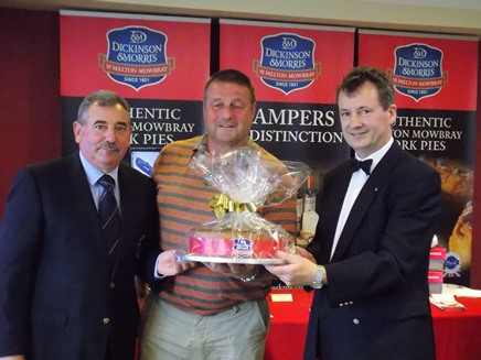 Stephen Hallam (right) and Club Captain Jack Inguanta (left) presenting Mark Lewis his prize for winning 'Nearest the Pie'